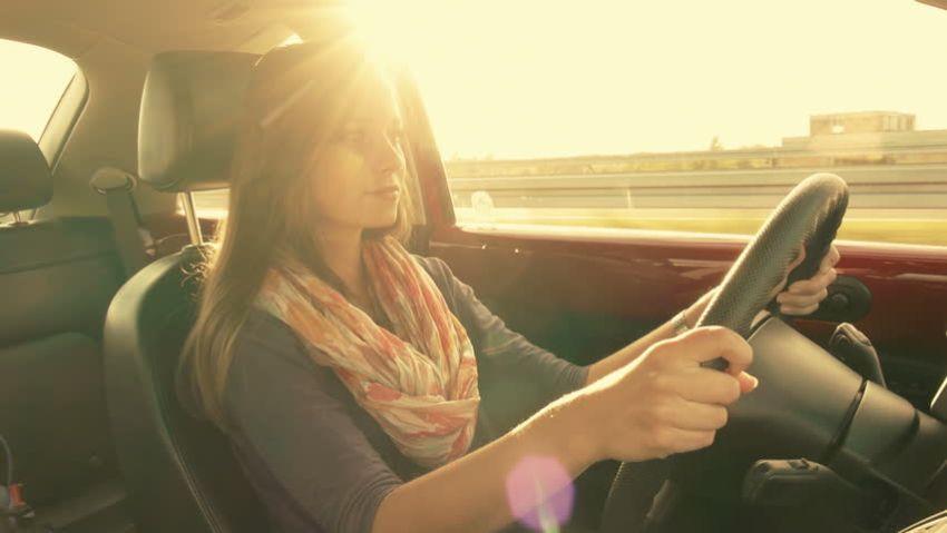 femme conduisant une voiture sous le soleil